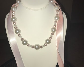 The Alison.   Glass pearl necklace with pink and white beads. Pink and white ribbons for the ties.