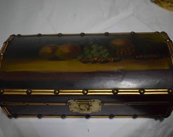 Box of wood with painted trunk shape and metallic trim.