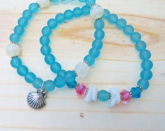 Ocean blue bracelet set with shell charm and pink detailing.