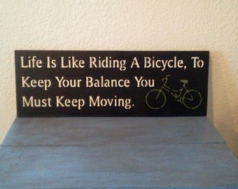 Life is like riding a bicycle, to keep your balance you must keep moving - Wooden Sign