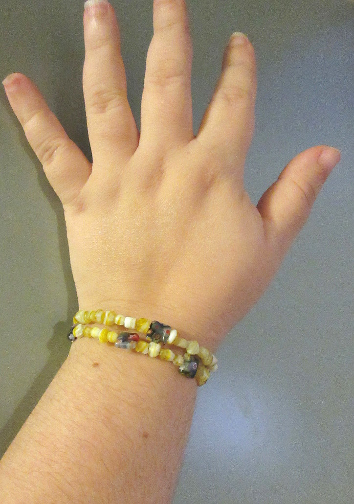 Yellow beaded sciart bracelet with floral accents that features the speed of light in meters per second squared.