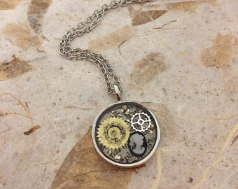 "Round Steampunk Resin Gear Recycle Newsprint Pendant with Cameo and Gears on a silver toned nickel free 20"" chain"