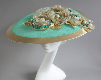 Emerald green and goldtone saucer derby hat with handmade flowers on comb