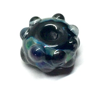 Lampwork textured focal bead in black, blues, and iridescent colors with dots of clear