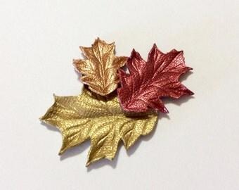 """Two 1.5"""" oak metallic leather leaves."""