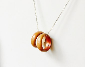 Two walnut wood ring necklace with a copper accent on a sterling silver chain.