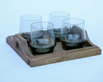 Four drinking glasses on a small wooden tray