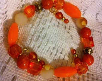 Orange beaded bracelet with Celtic knot beads.