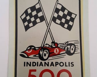 Vintage early 1960s wet transfer decal Indianapolis 500, crossed checkered flags and Indy racer, directions on back.