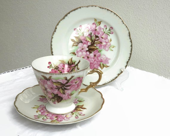 Cup, saucer plate with bunches of pink flowers, white china, gilt trim on edges and handle, Saji, Japan, mid century