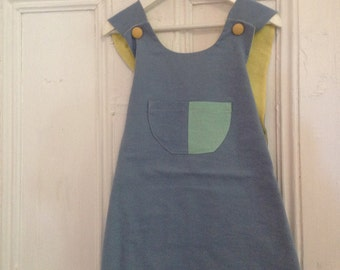 Hand dyed and hand sewn. Girls crossover dress. 100percent cotton. With a pocket on the front . Soft pastel colours. Blues and greens