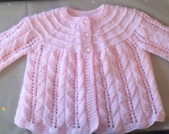 Pretty matinee jacket size 0-3 months.  Pretty lacey pink with a tiny thread of lurex through it.