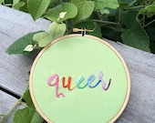 "Embroidered ""queer"" in pastel rainbow ombre on green"