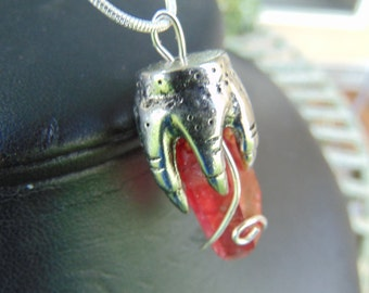 hand,pendent, holding red ,quartz crystal, heated to turn red