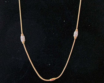 Gold tone chain with 2 plain elongated and 2 rhinestone elongated balls taged Preminer Desings with box
