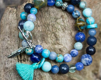 Blue bracelet on memory wire with tassel and metal feather