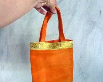 small orange gold fiber bag from India