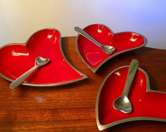 A trio of bright red heart metal serving pieces with silver heart shaped spoons