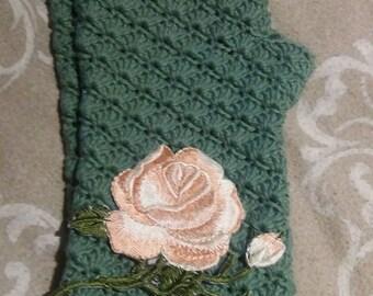 Matt green crochet fingerless gloves with soft pink rose.