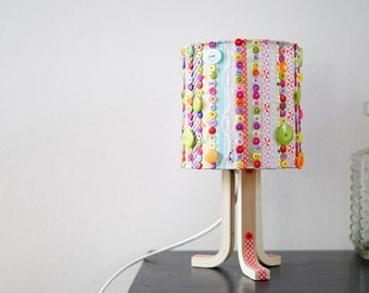 Seamed small model, lamp in ribbons and buttons sewn hand