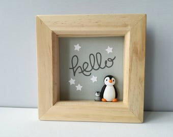 Box frame miniature penguin and chick. Hello. Grey and white paper cut.