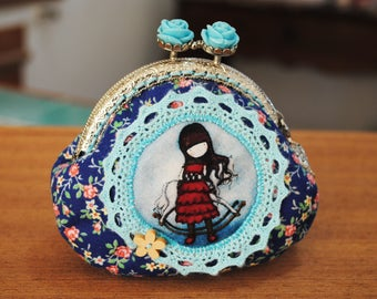 """Purses in patterned fabric flowers on blue, with image of girl collection """"Just Gorjuss""""."""