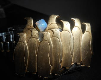 Gold tone penguins on a stainless steel band fits 8 in  or loosely fitting upon the hand is a fun  piece of art .