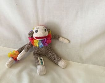 Baby sock monkey with silk flower lei on neck and tail.
