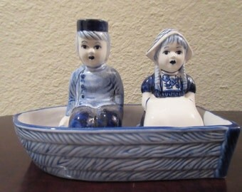 Sweet Delft Blue and White Salt and Pepper Shakers. This is a 3 piece set of a Dutch boy and girl (S&P) sitting in a boat. Precious!