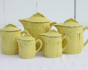 French vintage set of five jugs in yellow