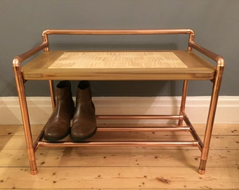 Copper pipe bench with lower shoe storage and reclaimed wood top in an industrial style