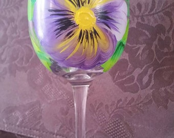 Wine glass hand painted with purple pansies.