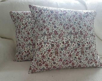 A pair of red floral cushions