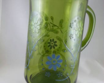 Green retro pitcher with floral pattern painted on side.