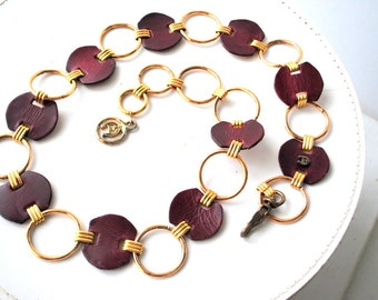 Disco vintage 70s belt with a metal a burguny genuine leather circlesand discs.Made by Etienne Aigner.