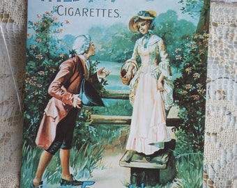 1977 Postcard. Wild Woodbine Cigarettes Add. Printed in England. Man and Woman in Rococco Dress in a Garden. Envelope Included.