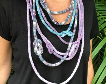 Pastel color necklaces. Four skinny scarves knit w very soft to the touch silk merino yarn hand-dyed lilac, sky blue, lavender & variegated