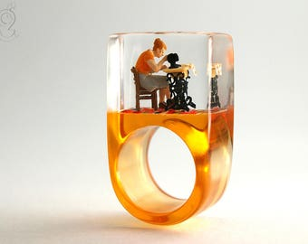 Sewing Machine – Handmade sewing ring with a mini seamstress and her sewing machine on an orange ring made of resin