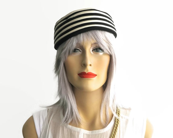 Vintage pillbox hat, black velvet crown with ivory colored and black satin piping around the side, fully lined, open size, circa 1960s