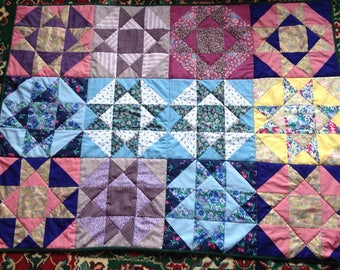 Lap quilt with pretty patchwork front and a lovely green backing fabric depicting butterflies, etc.   Handcrafted
