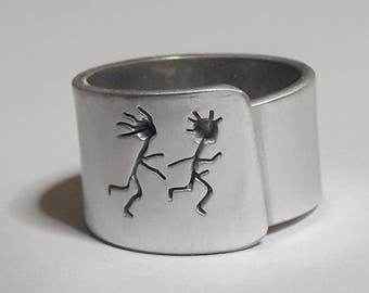 Adjustable aluminum band ring with: She follows him, and custom text.