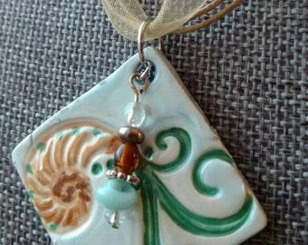 Nautilus scroll with seaside pendant