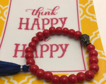 Bold Red beaded flexible bracelet with a Pewter Buddha Head and Blue Tassel.