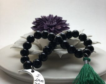 I Love You To The Moon & Back! Jet Black beaded flexible bracelet with ILYTTMAB moon shaped charm and Emerald Green Tassel.