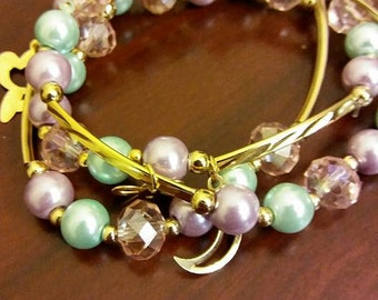Shiny Bracelete handmade,gold, aqua and lavander colors.beautiful Bracelete size adjustable.flower,moon, bow charms