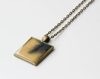 Sparkly gold with a splash of deep blue resin square pendant.