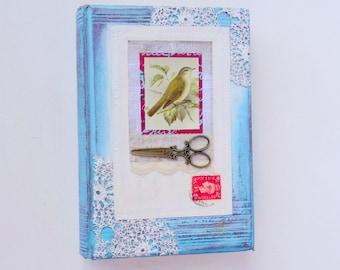 Original artwork. Mixed media altered book art. Collage with vintage bird, scissors, postcard & lace. Book lover gift. Blue, white, red.