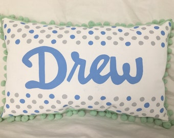 Pillow with blue and gray polka dots and name in blue