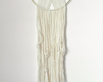 Modern macrame wall hanging, yarn crisscrossed on ring