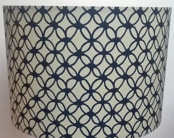 Handmade lampshade with repeated cream and navy blue, macrame inspired, circular geometric pattern